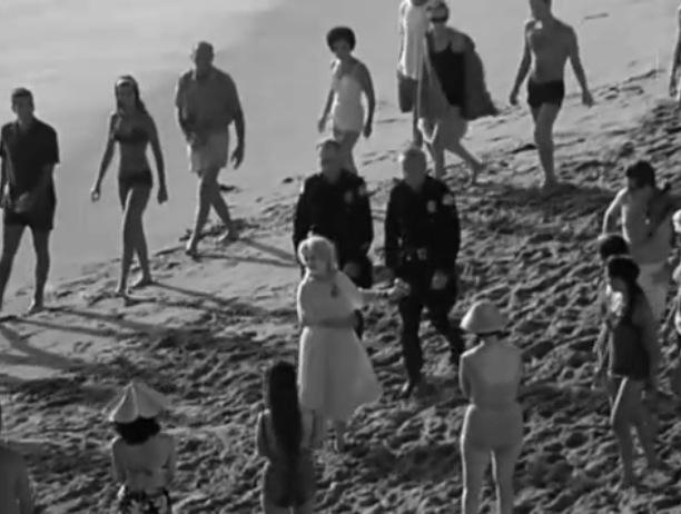Beach crowd gathers far off shot