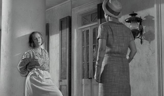 Velma greets Miriam on porch