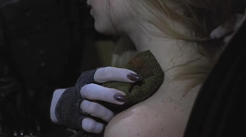 Lemora's black nails touching Lila's flesh