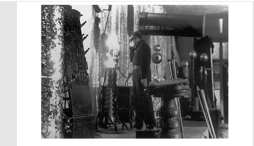 """Standing fearlessly before a high voltage arc.His reliable switchboard can be seen in the foreground while the famous """"Meg Senoir"""" Tesla coil appears in the background"""