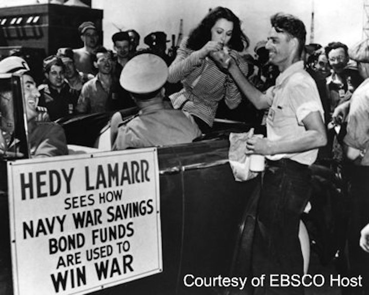Hedy Lamarr with shipfitter Richard Spencer, as she tries to boost War Savings Bond sales by touring the Philadelphia Navy Yard in Pennsylvania circa 1940s
