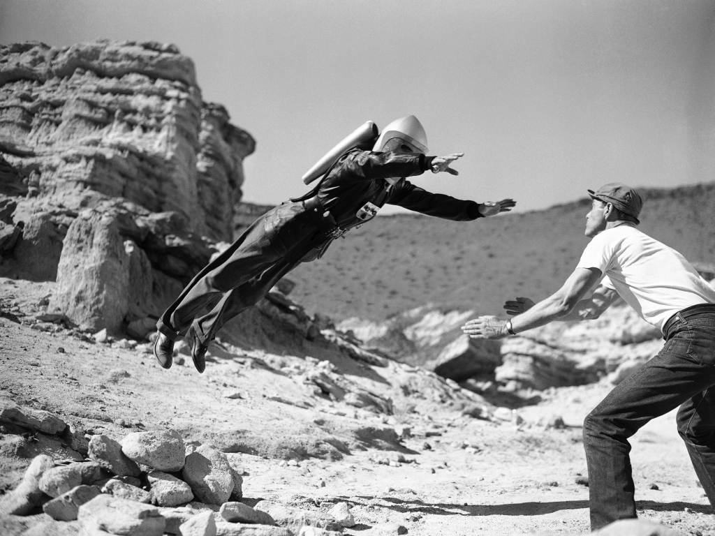 """""""Commando Cody, the Sky Marshal of the Universe,"""" aka, George Wallace, appears to defy the laws of gravity, for a moment at least, as he lands in the arms of a prop man during production of the film """" Radar Men from the Moon,"""" at Red Rock Canyon in the Mojave Desert, 80 miles northeast of Hollywood, Calif., Dec. 12, 1951. Gravity may be defied in some the new movie serials based on the fantasies science fiction, but what goes up still comes down, even if the film wont let you see it. (AP Photo)"""
